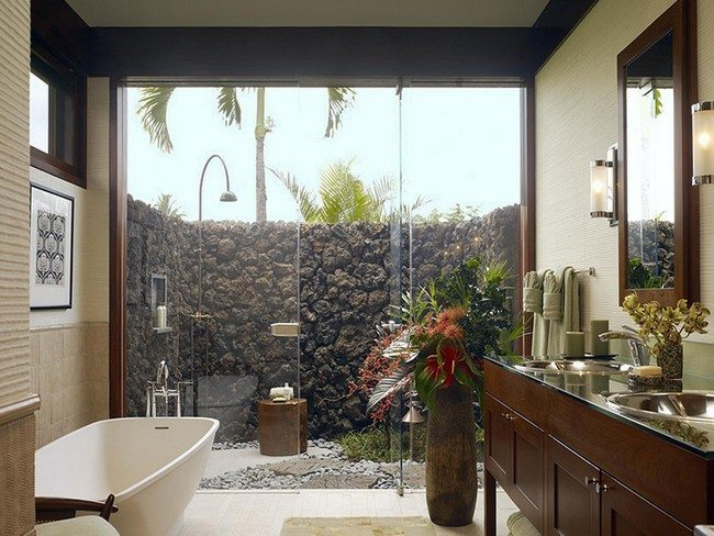 bathroom with open glass wall. stone fence behind the bathroom. white sink ande wooden shelves for towels