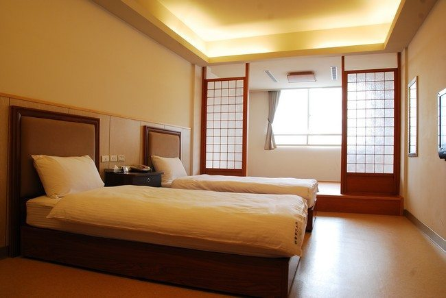 japanese hotel with tow single beds with decorative wooden doors