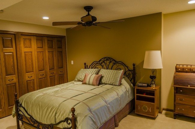 basement bedroom design with dark iron bed frame, brown laminate sideboard lamp, brown varnished wooden door with brown wooden chest of drawers