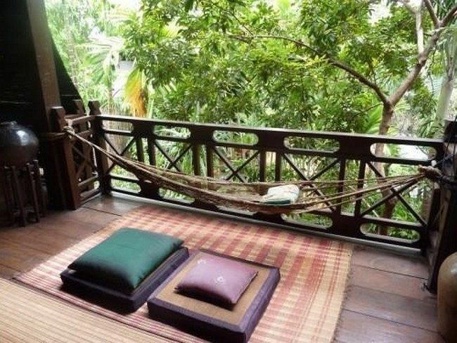 asian open balcony with cushhhion and hammock