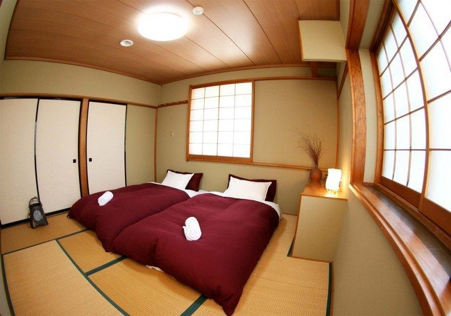 red double bed with white pillows. doors made from bamboo