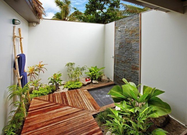 outdoor shower with wooden path to it and live green vegetables