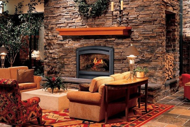 fireplace in the living room? made from stone . surfaced by decorative tile, bright cerpet ont he floor, theree seater sofa. magazine table behind it