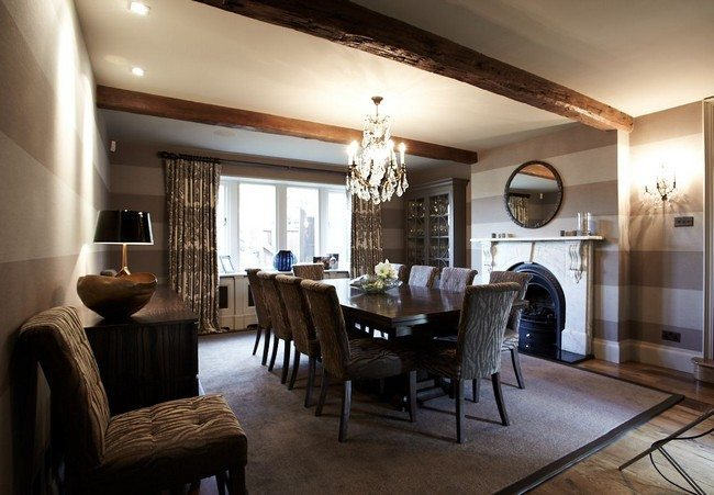 Diing Hall with beams under the ceiling with long blacj table for 8 person, in fron of the fireplace