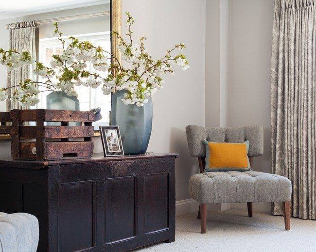 brown chestdraw with blue vase and soft small armchair with yellow cushion