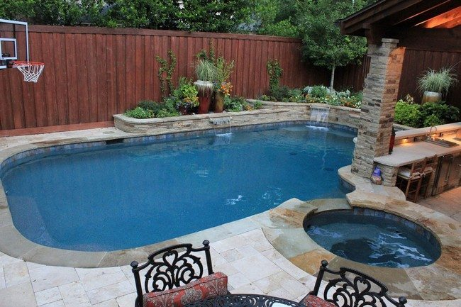 backyard with two pools with the wooden fence behind