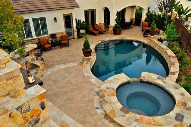two pools in the backyard covered with the stome tiles