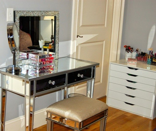 mirrored makeup table with two drawres and mirror on the wall