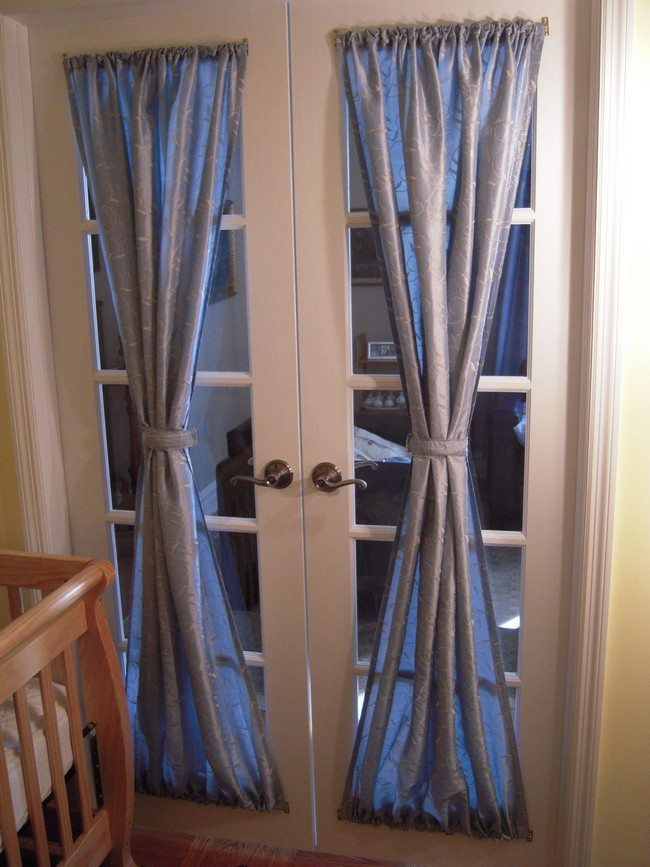 Plastic french doors with blyu curtains tied up together