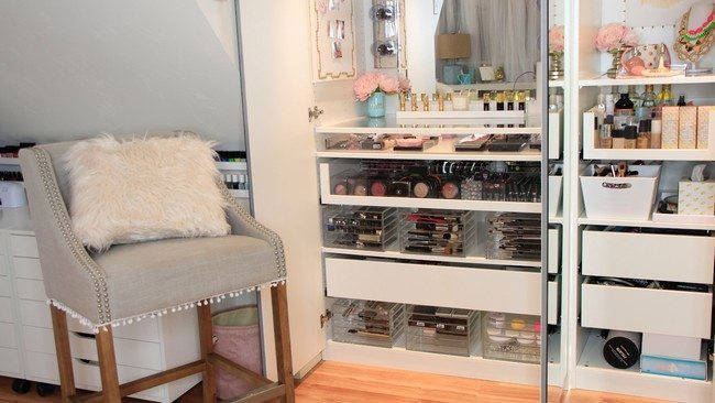 mirrored makeup storage with different sheleves full of cosmetics and small chair