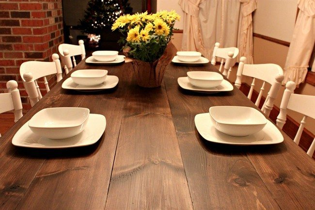 wooden table with white chairs and white dishes on it