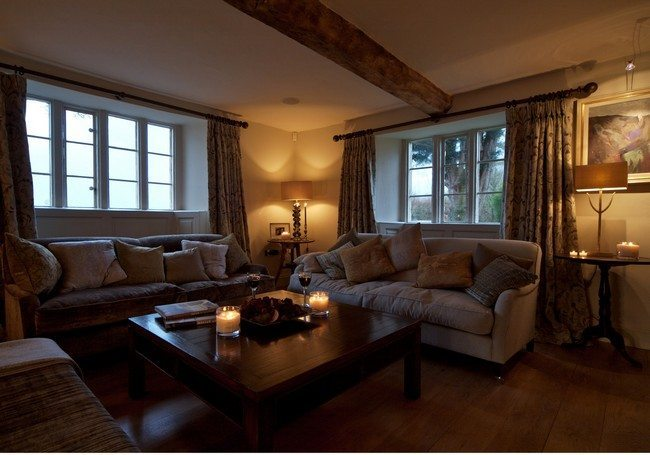 Farm house with wooden beams under the ceiling and two sofat 2 or 3 seater sofas with wooden tea table between them