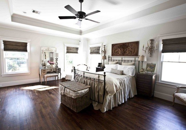 single bed with metal back and the top on the wooden floor and a fan under it