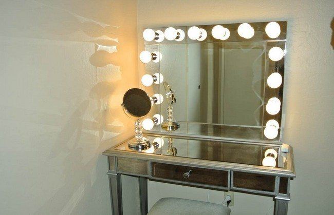mirrored makeup storagetable with lights around the mirror on the wall