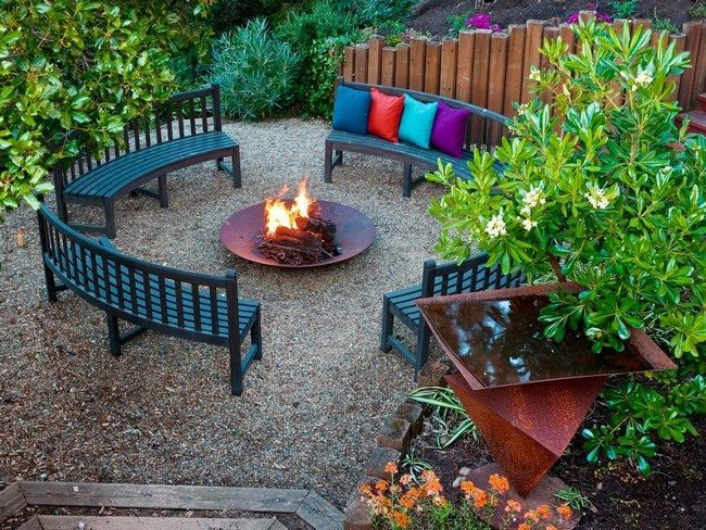 Place for fire with benches around fireplace covred with multicolor cushions