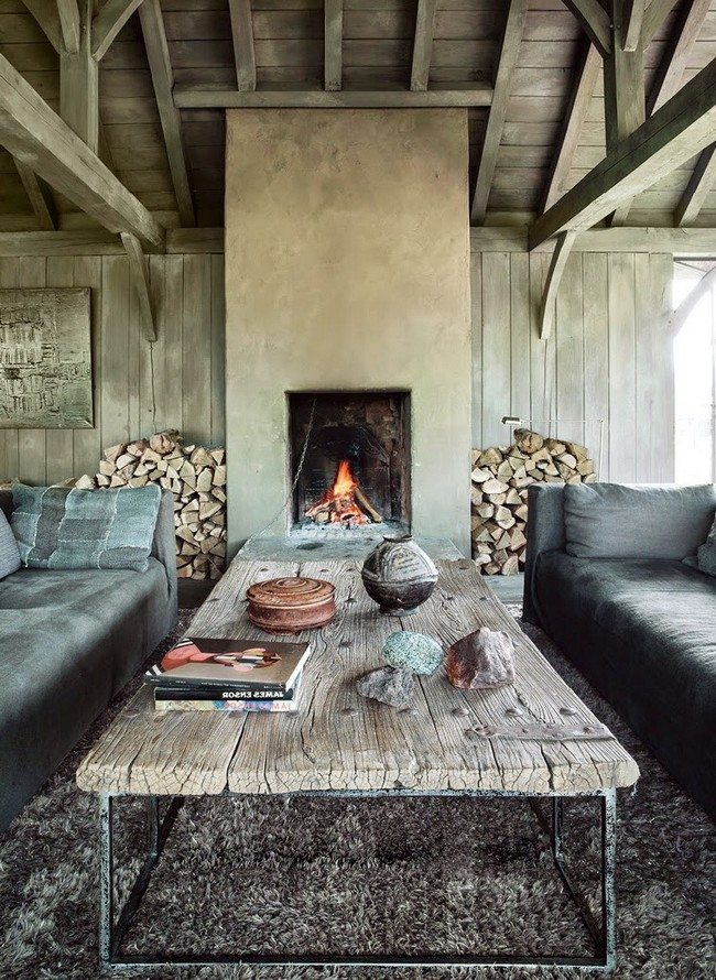 Two long soft sofas with wooden table and live fireplace and woods on the left and grey carplet