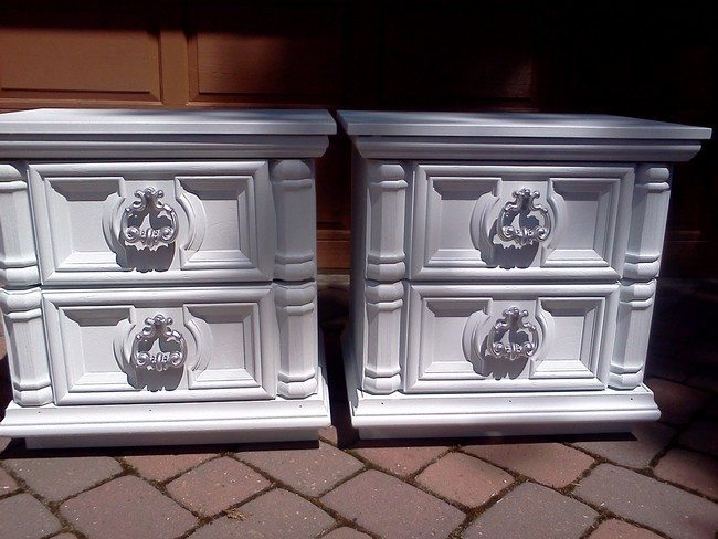 two white classic night stands with the handle as a lion head