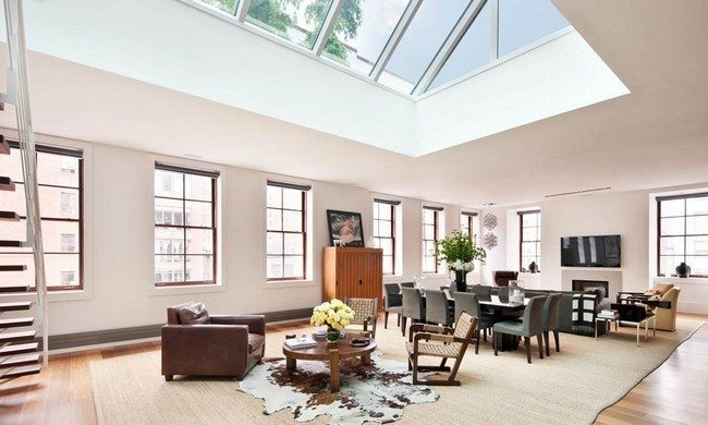 : A modern-looking living room with many windows and fancy rugs