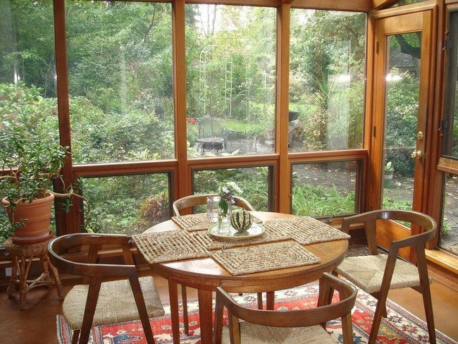 Small sunroom with simple, polished wooden furniture and a beautiful view of the garden