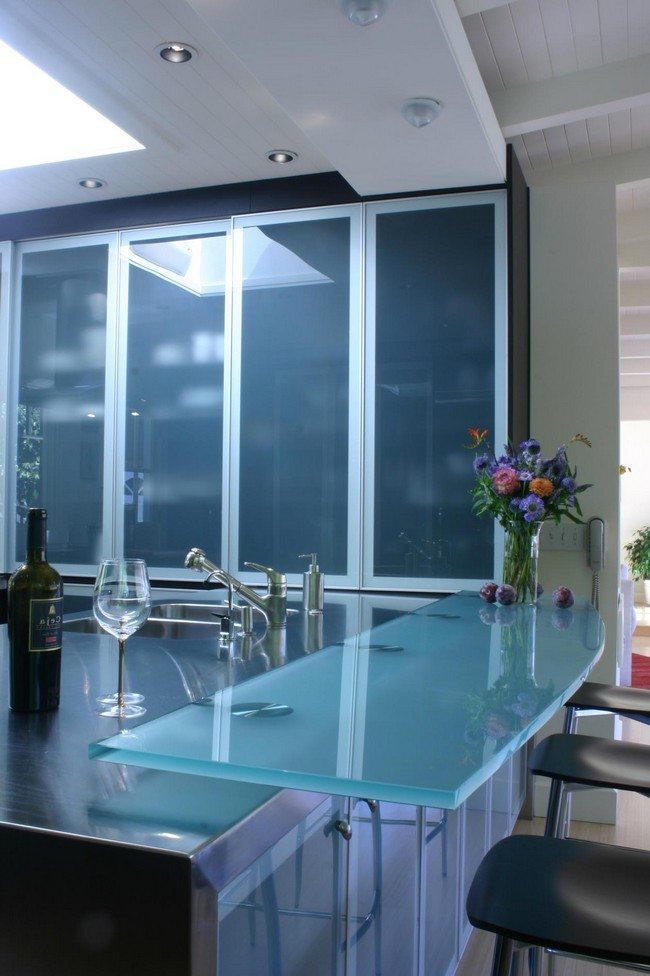 Frosted doors for the cabinets are used with a glass table to give the room an all-glass look