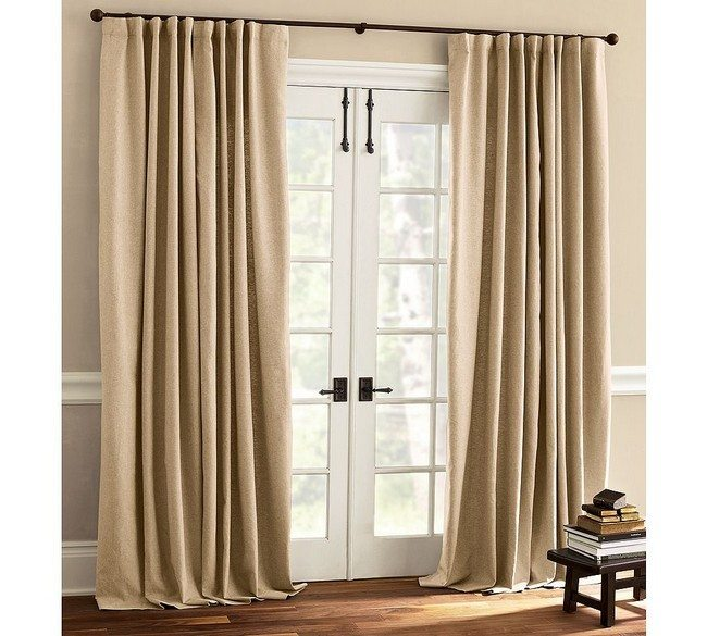 wooden white doors with brown metal handles with solid creme curtains