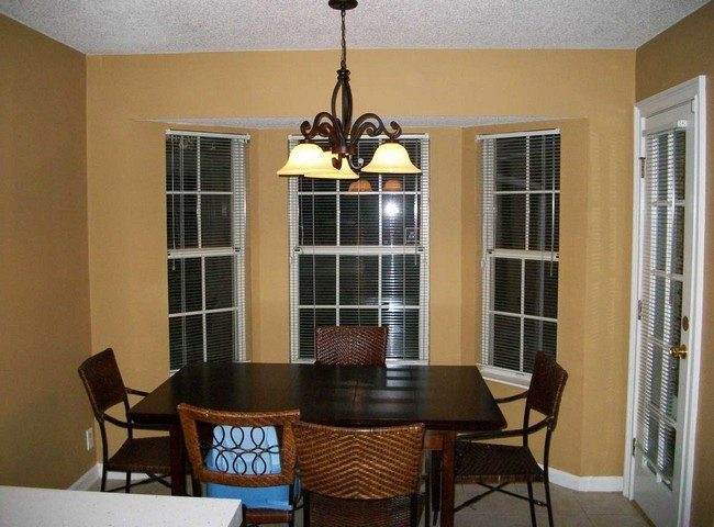 Glass Door With Horizontal Panels. Dark Wooden Table. White Dining Chairs.  Rectangular Dining Table. This Customized Overhead Lighting Fixture ...