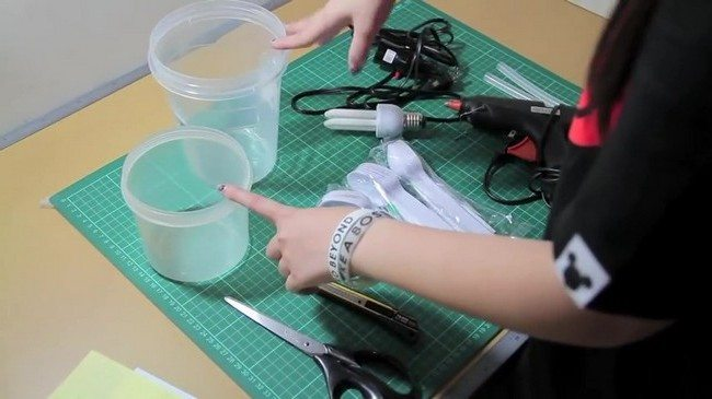 The materials needed to create a DIY lamp from plastic spoon, a glue gun, a bulb, cables and some extra