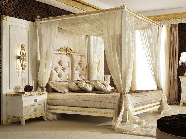 Sheer white curtains surrounding four-poster bed