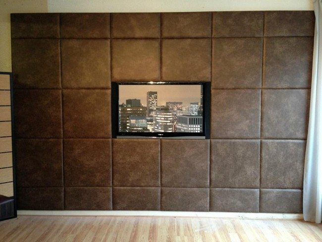 Television Screen Mounted On Brown Tufted Wall Panel