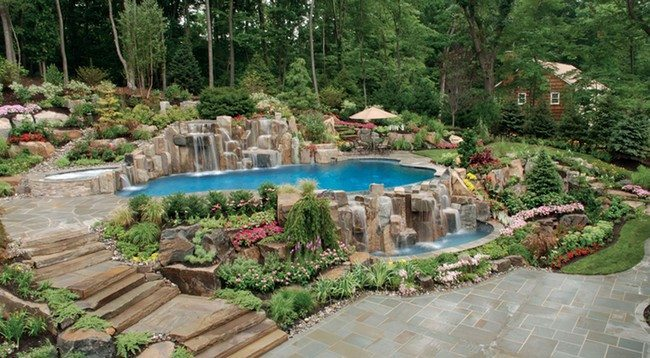 Pool waterfall ideas you can recreate in your backyard decor bright flowers growing around the swimming pool solutioingenieria Gallery