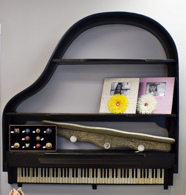 Piano mounted on wall to create a unique bookshelf
