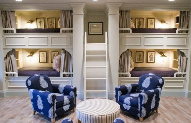 The grey drapes covering the bed area and the upholstered furniture add class and elegance to this bunk room