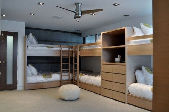 Bunk beds attached to the wall to create space in the center of the room