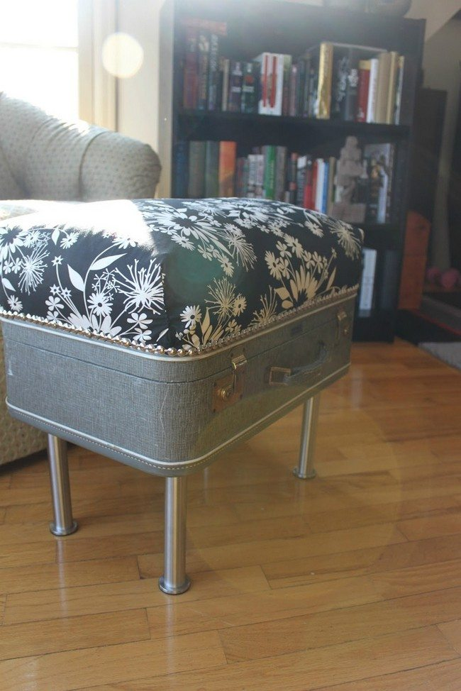 Old suitcase converted into small, upholstered coffee table