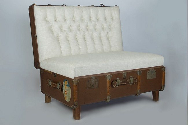 Old suitcase upholstered into a chair with four wooden stands