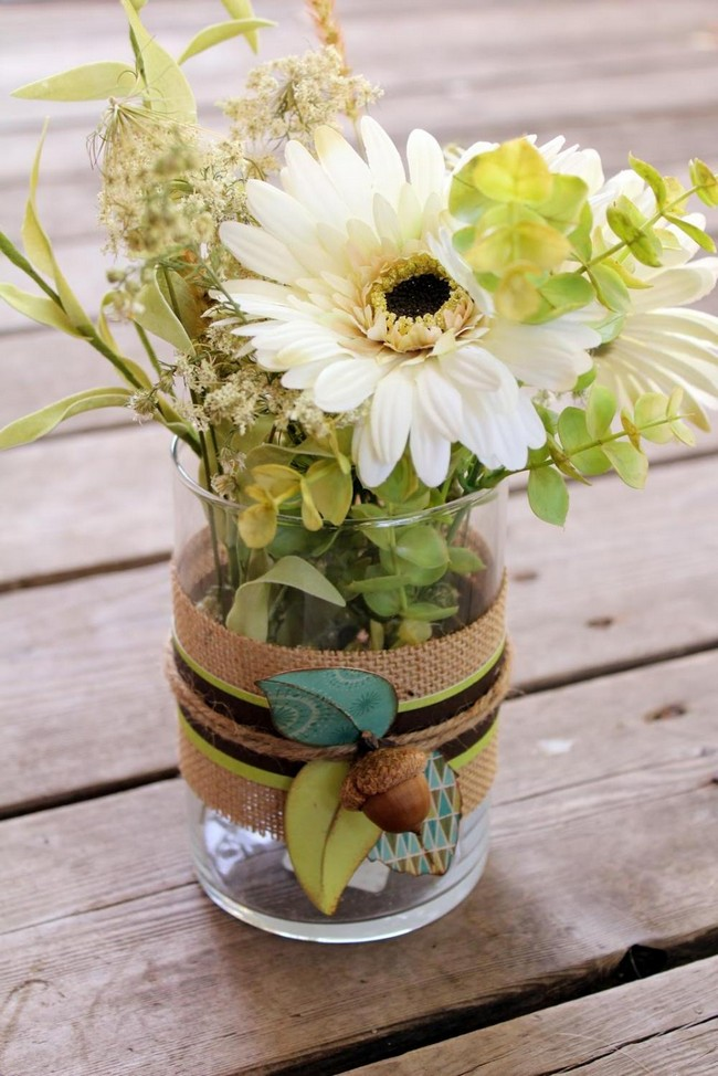 Simple glass vase decorated by wrapping ribbon, rope and flower detail on the exterior