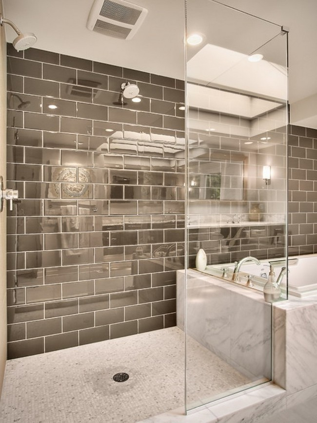 : Light grey veined marble tiles paired with dark grey subway tile on the wall
