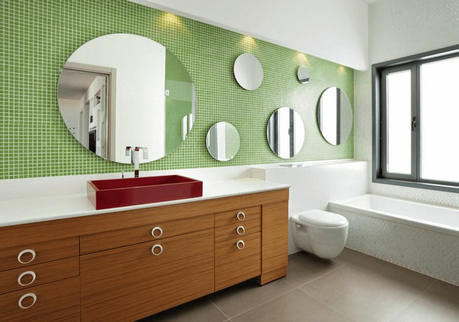 Series of round mirrors in different sizes placed on a mosaic tile wall
