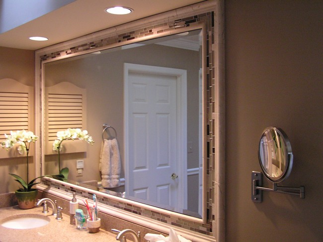 Large mirror encased in a neutral-colored tile frame, with in-ceiling lighting