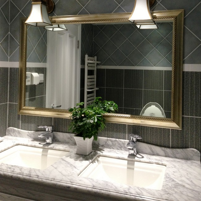 Mirror with neutral-colored frame placed against grey tile in different shades and designs