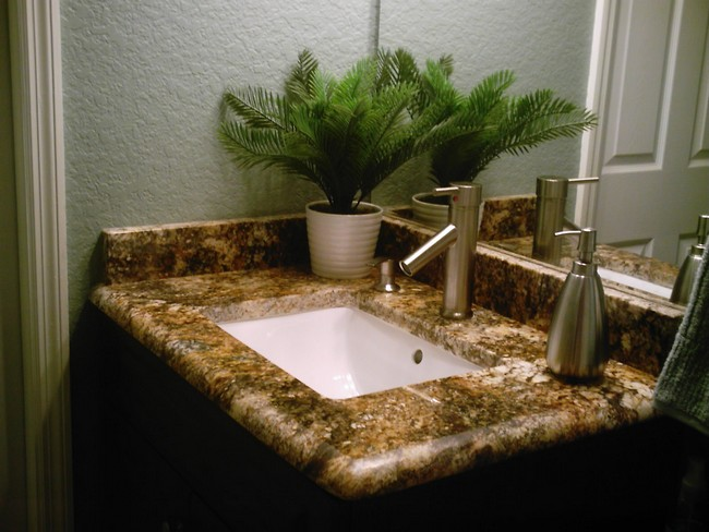 Small brown marble countertop embedded with white marble sink