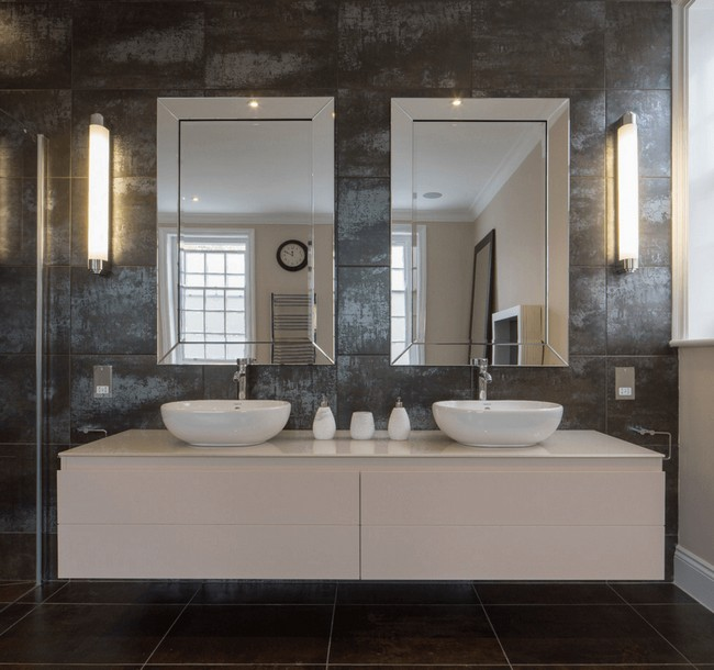Twin Mirrors Placed Against Grey Mosaic Wall