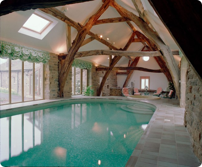 Indoor pool in rustic-style room with wooden beams and stone wall