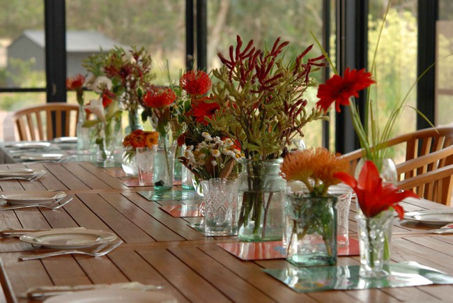 Row of water-filled glass vases immersed with flowers