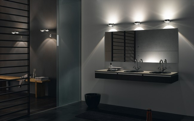 Dimly-lit bathroom with illuminating lights above the mirror