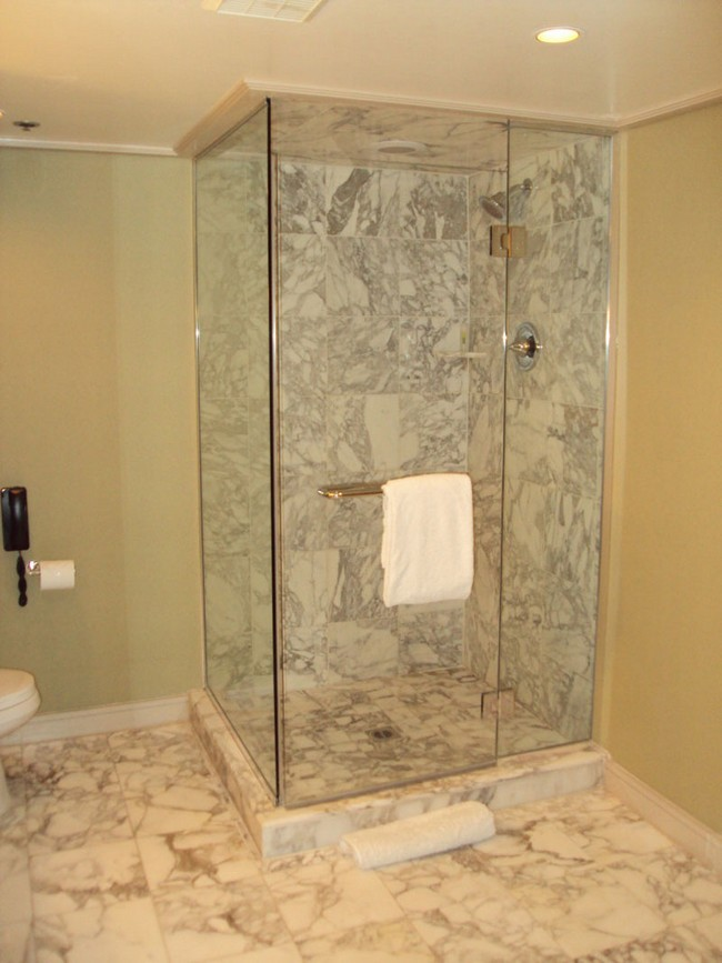 Shower area with marble tiles and glass wall
