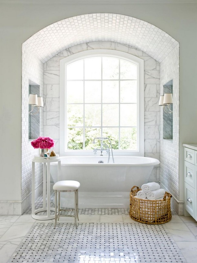 White-themed bathroom with large marble tiles on the floor, marble skirting board and a giant window streaming in natural light