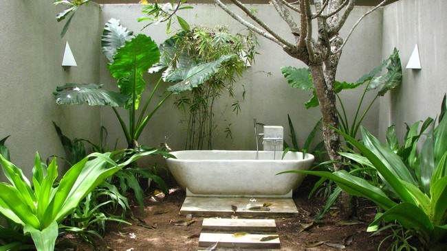 Outdoor bathtub in the corner of the garden, with white terrace steps