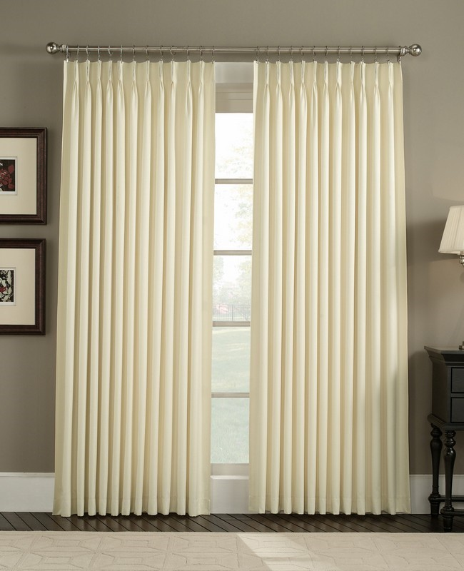 Ivory curtains with elegant design on a metallic holder against light grey walls