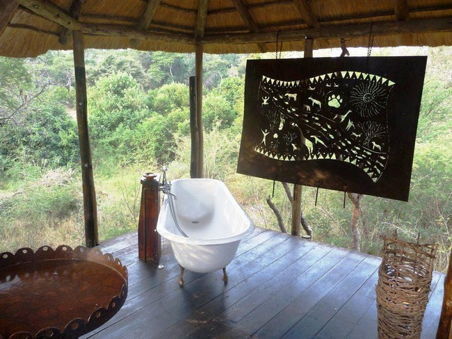 Bathroom with an art piece in the middle of a lush forest
